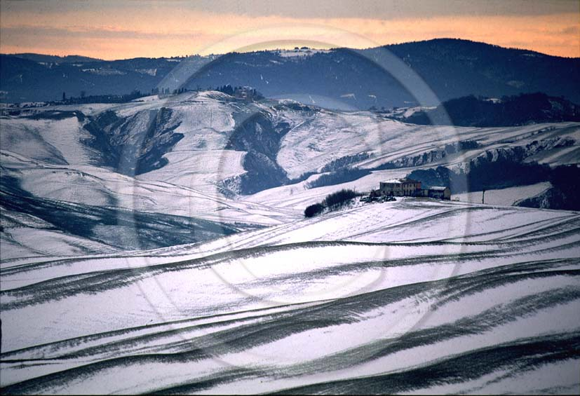 1989 - Landscapes of farm and Crete senesi with snow a bit before sunrise in winter, near Muciglaini place, 6 miles south the province of Siena.