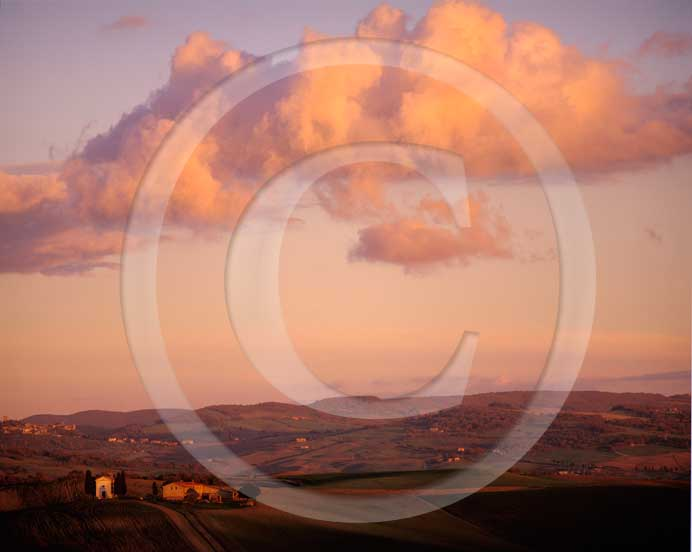 2003 - Landscapes of church and farm with orange clouds on sunset in autumn, near Pienza village, Orcia valley, 20 miles south the province of Siena.