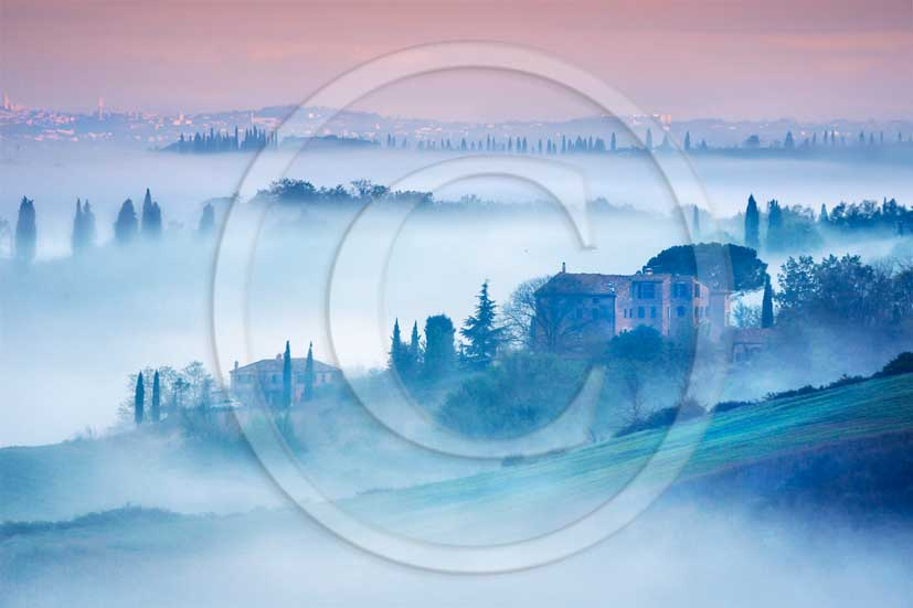 2013 - View of a fog early morning of the country and hills near san Giovanni D'Asso village in Crete Senesi land.