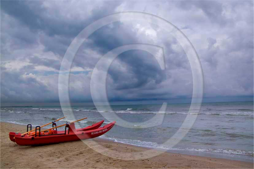 2008 - View of beach in Tirreno sea with red boat and white and grey clouds before a thunderstorm in winter, near Calambrone village, 4 miles north the province of Leghorn.