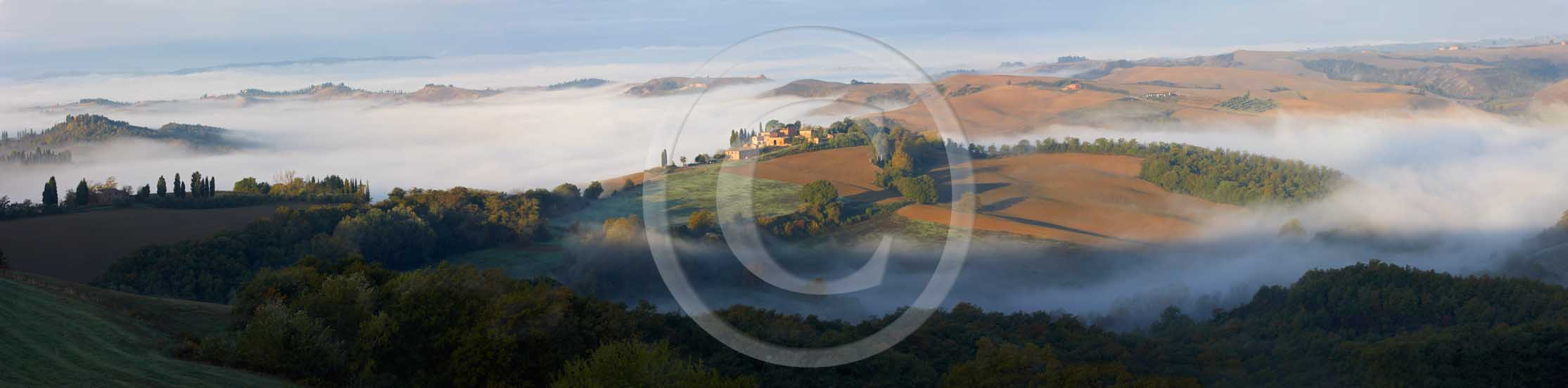 2008 - Panoramic view of landscapes and farm with fog on sunrise in winter, Montemori place, near Asciano village, Crete Senesi land, 18 miles south province of Siena.<br />