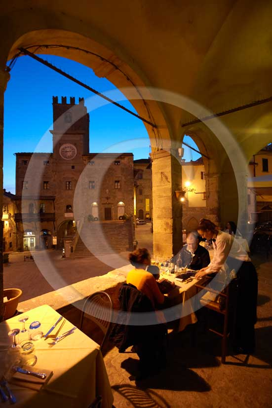 2009 - People at restaurant in the main square of Cortona medieval village with the Council Palace on background, Val di Chiana valley, 21 miles east Arezzo province.