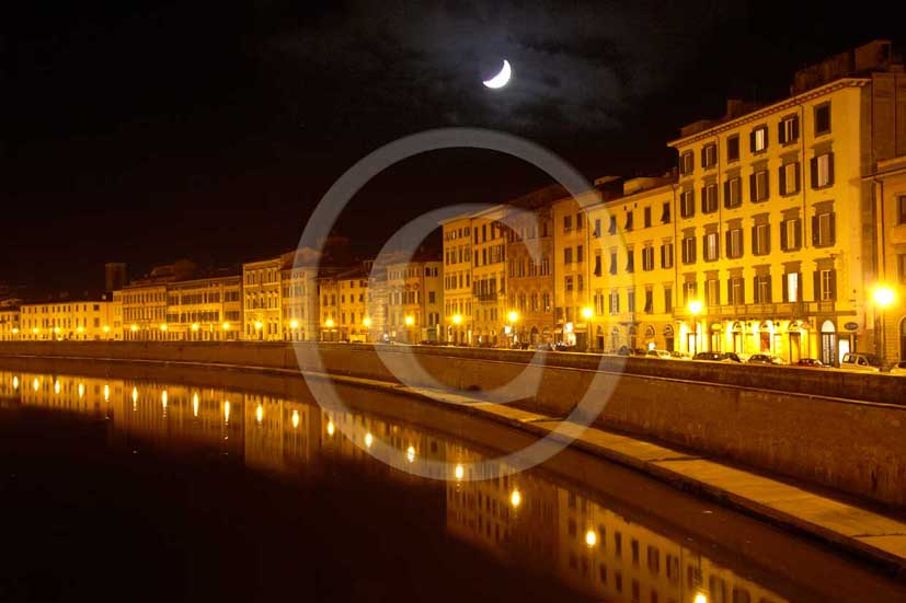 2009 - Night view of the main street of Pisa town with Arno river and the moon in winter.