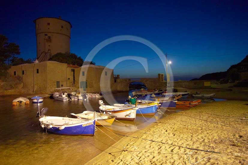 2009 - Night view of the beach, old fisher's boats and the tower of Campese of Isle of Giglio on summer, Maremma land, 80 miles south the province of Grosseto.