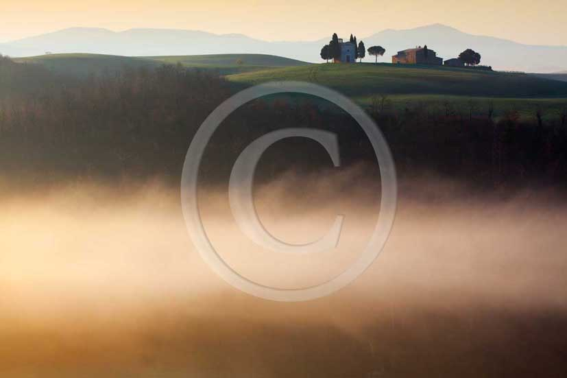 2009 - Landscapes of farm with country chapel and cipress with fog on sunrise in winter, near S.Quirico village, Orcia valley, 22 miles south province of Siena.
