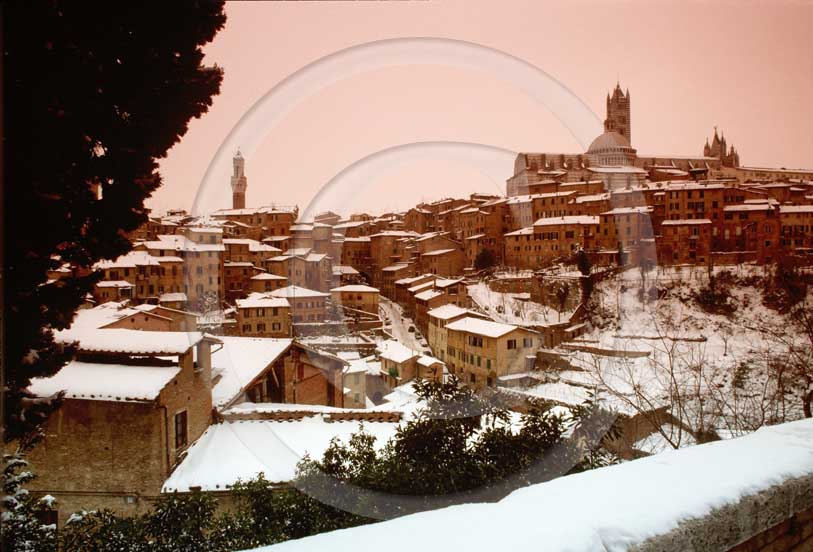 1985 - View of Siena medieval town under snow on late afternoon in winter.