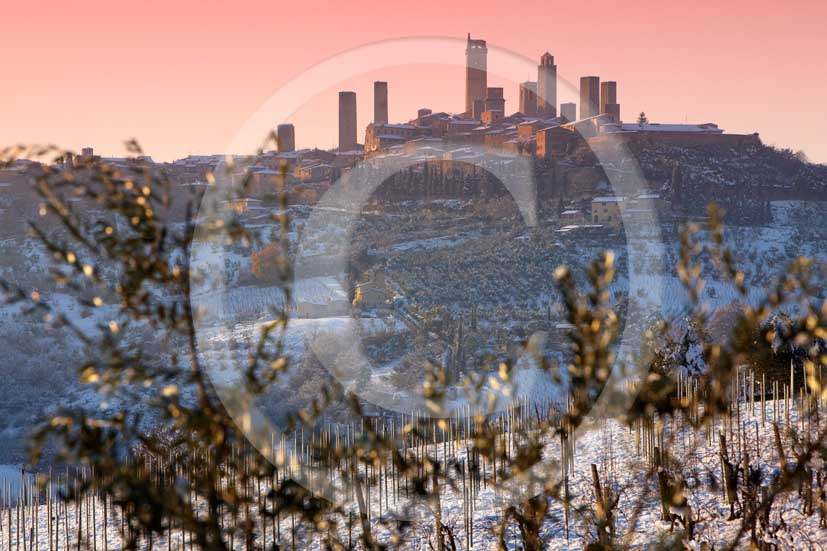 2009 - Surrounding country viewer of San Gimignano medieval village with the main towers under the snow in winter on sunrise, Chianti land, 19 miles north Siena province.