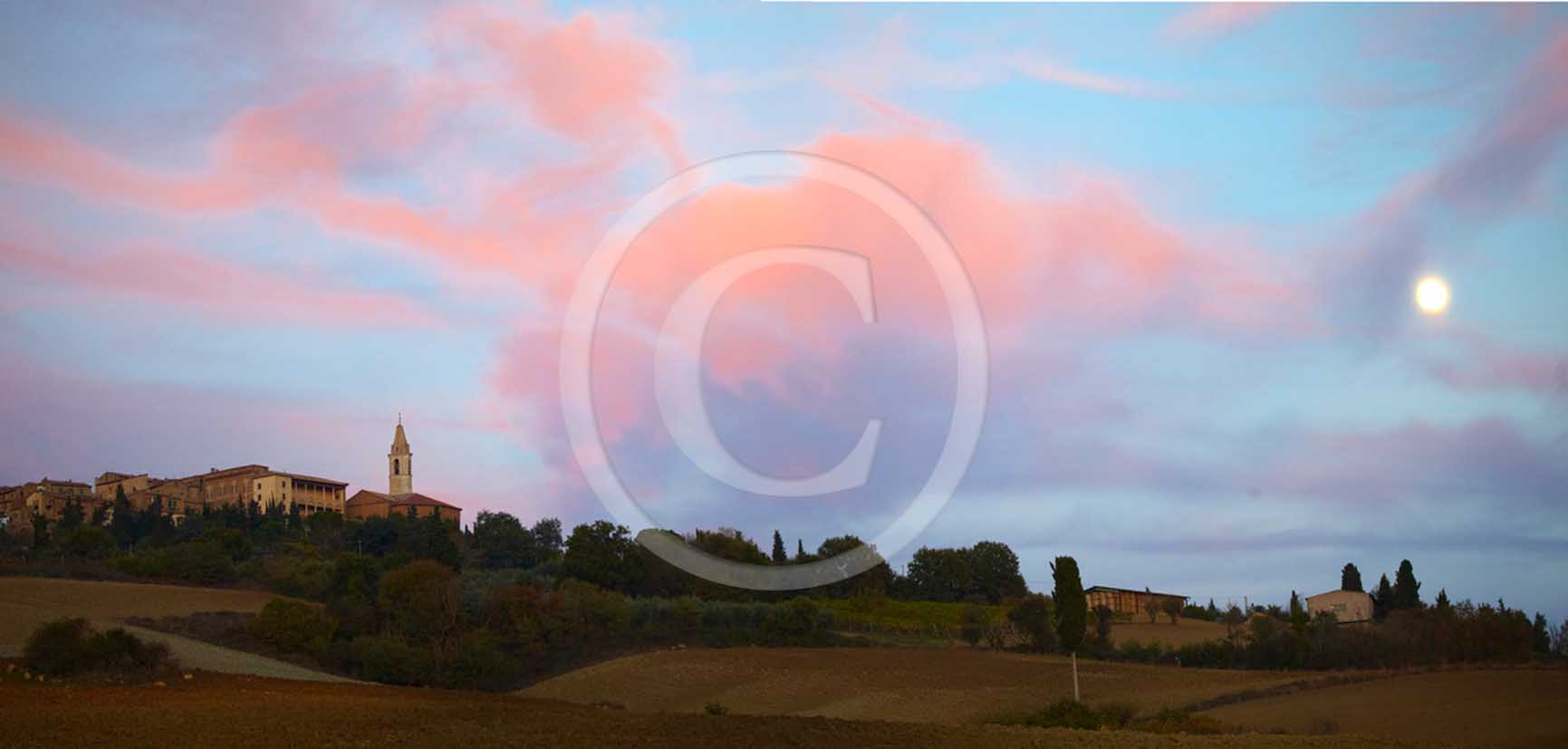 2011 - Panoramic view on sunset with moon and orange clouds of Pienza medieval village in Orcia valley.