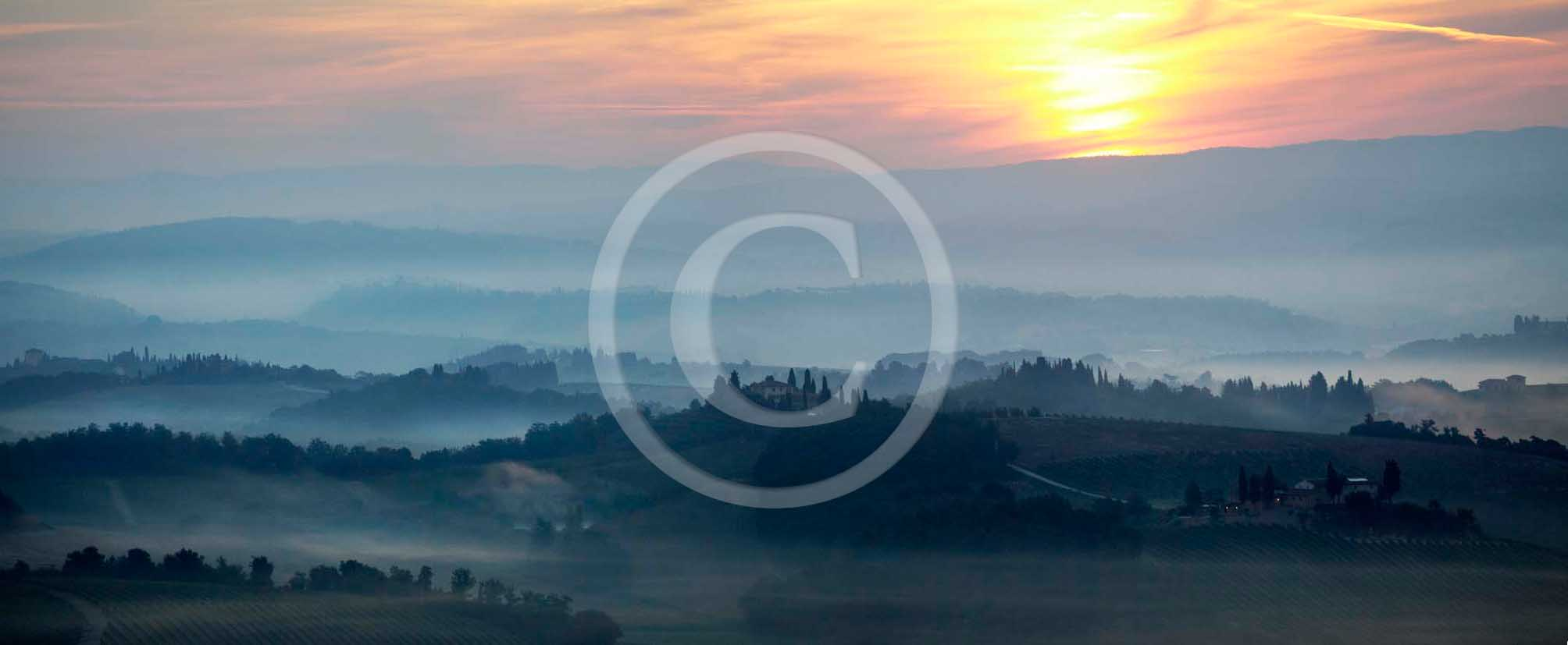 2011 - Panoramic view of cipress and tuscan skyline at sunset in Orcia valley.