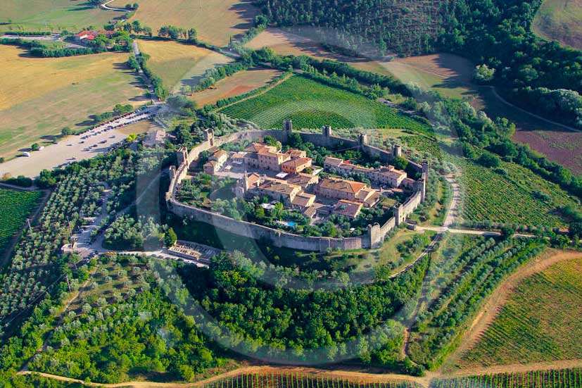 2011 - Aerial view of Monteriggioni medieval village with green vineyards in Chianti Classico land.